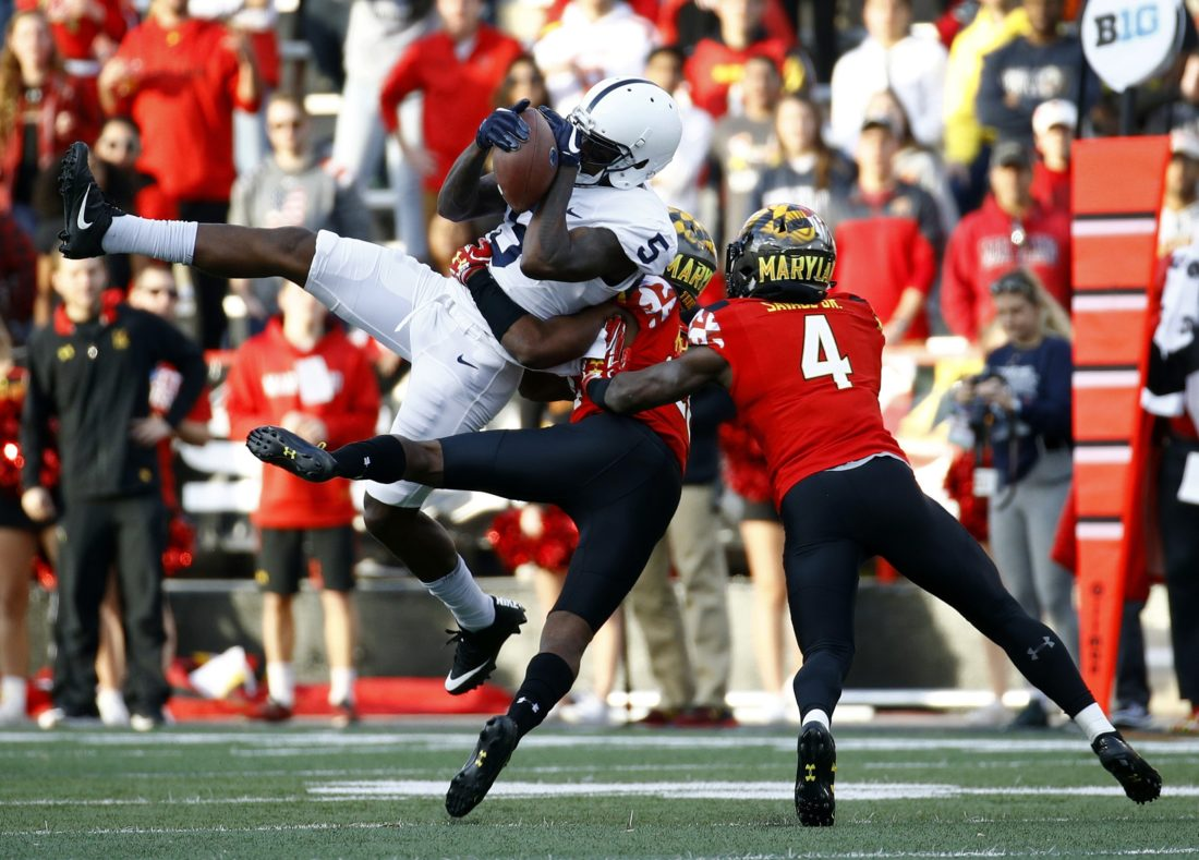 ASSOCIATED PRESS Penn State wide receiver DaeSean Hamilton (5) catches a pass as he is pressured by Maryland defensive backs Antwaine Richardson, center, and Darnell Savage Jr. in the first half Saturday at Maryland.