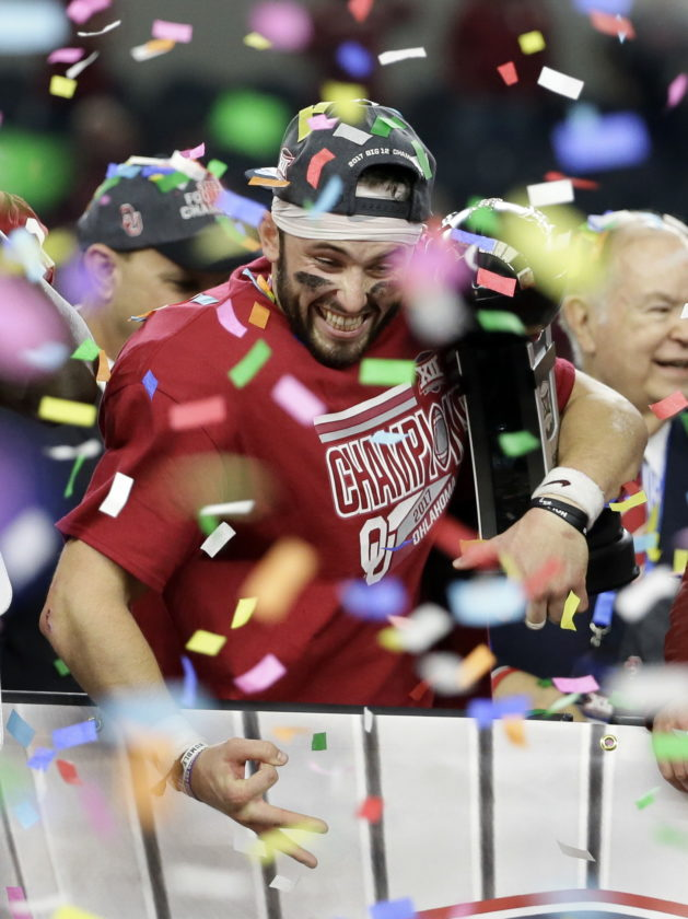 Oklahoma quarterback Baker Mayfield, center, holds his Most Outstanding Player trophy as he celebrates with the team after their 41-17 win in the the Big 12 Conference championship NCAA college football game against TCU on Saturday, Dec. 2, 2017, in Arlington, Texas. (AP Photo/Tony Gutierrez)