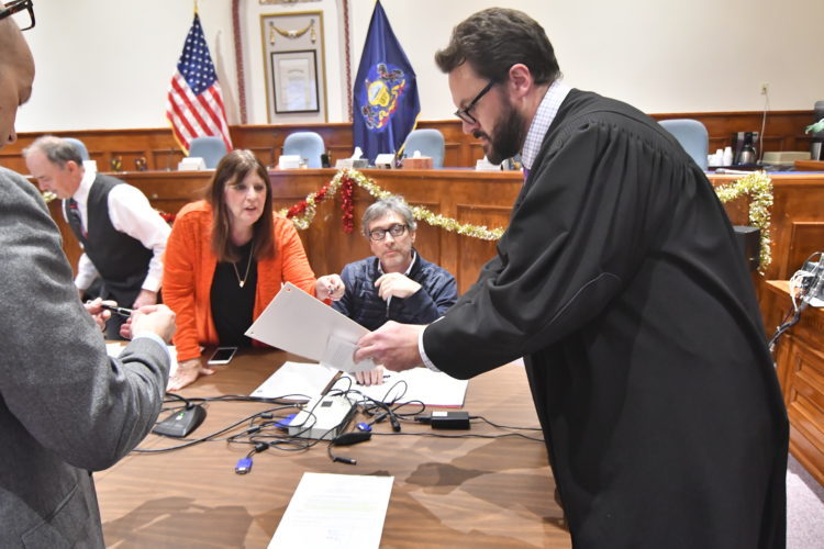 MARK NANCE/Sun-Gazette Williamsport City Clerk Janice Frank, left, hands paperwork to District Judge Christian Frey, as Tony Nardi looks on before members of the Charter Commission were sworn in at City Hall Wednesday.