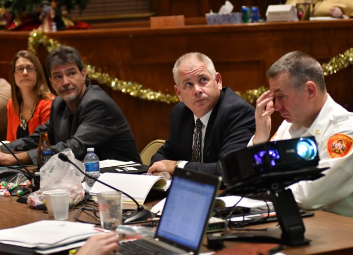 MARK NANCE/Sun-Gazette From left, Megan Page, human resources director; Joe Gerardi, department of codes; Police Chief David Young and Fire Chief Todd Heckman watch the city budget presented on a screen during the first reading of the city budget Thursday night.