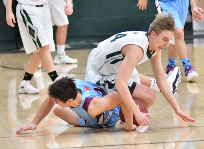 MARK NANCE/Sun-Gazette Loyalsock's Connor Watkins, (4) and Hughesville's Matt Myers (14) wrestle for the ball in the second quarter Tuesday at Hughesville.