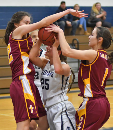 MARK NANCE/Sun-Gazette Muncy's Makenna Snyder (25) is smothered by St. John Neumann's Abigail Henderson (32) and Gabrielle List (1)  in the first quarter Friday at Muncy.
