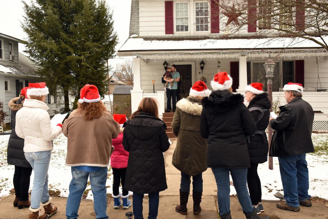 JUDI PINKERTON/Sun-Gazette Correspondent The Serenity Singers serenade a city resident and child Sunday.