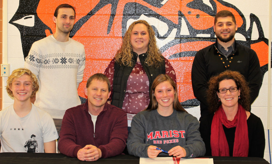 Jersey Shore senior Emma Butzler (center) signs her letter of intent to continue her swimming career at Marist College.  Pictured alongside Emma are her parents Tom (left) and Kelly, and her brother Alex (far left).  Standing in the back are, from left, Jersey Shore high school swim coaches Jon Palumbo and Jenna Brooks and Jersey Shore athletic director Stephen Alexander.