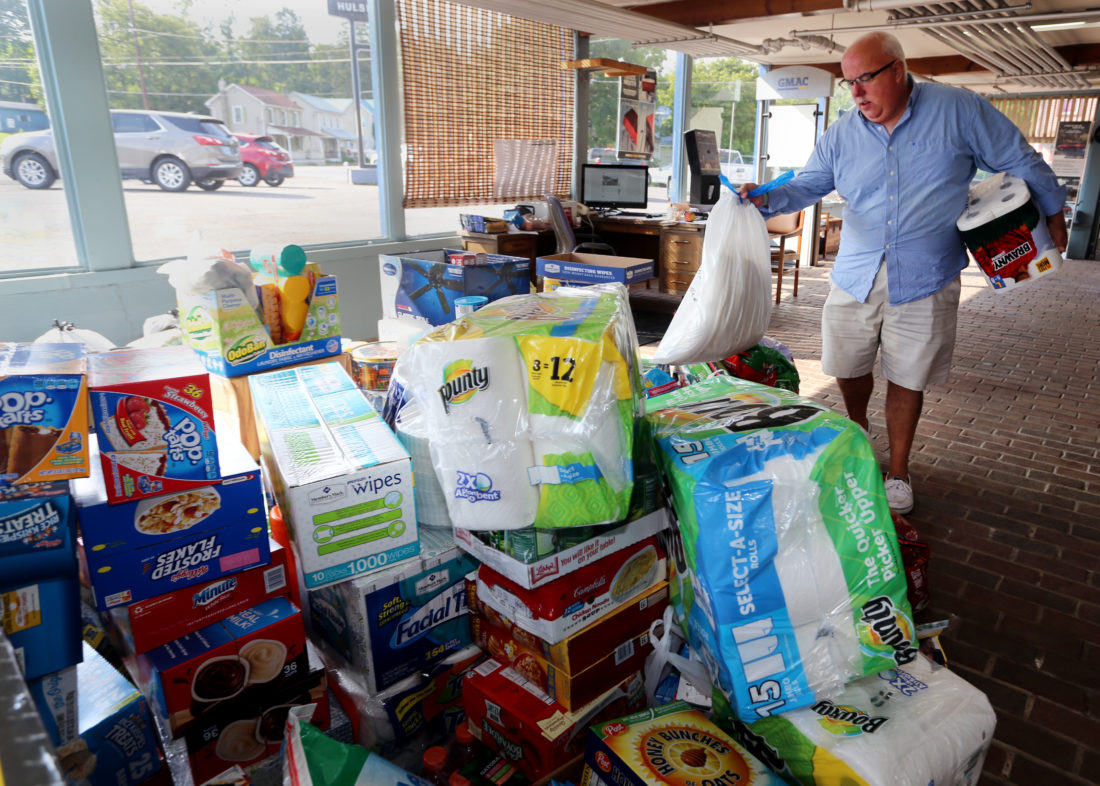 """Chris Hann, a salesman at Hulsizer Chevrolet in Montgomery, stacks a few of the many donations that fill a large part of the showroom floor at Hulsizer's at 2350 Route 54 Hwy, Montgomery. The dealership put the word out on Tuesday that they would be accepting donations for hurricane relief until 6pm Friday. Hann, who is spearheading the collection, """"A friend of mine contacted me who is involved in the actual organization that's taking it down , so I asked our owner Bill Schneck, he was excited about doing it because it's a chance to give a little back. """" The donations will be driven by pickup trucks and trailers from Montgomery to a waiting tractor trailer in Swoyersville before heading to Texas.  The family owned dewalership Hulsizer Chevrolet has been in Montgomery for 117 years and has seen it's share of flooding through the years according to Hann. As one of the residents dropping off cases of water pointed out, Montgomery residents know how devastating a flood can be and welcome the opportunity to help others in need. KAREN VIBERT-KENNEDY/Sun-Gazette"""