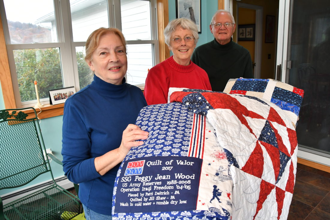 MARK NANCE/Sun-Gazette Pat Golla, of Catawissa, left, Bonnie and Jim Fiedler, of Bloomsburg, show off some of the dozen quilts which are made by the Columbia County Quilts of Valor for U.S. veterans. The quilts are made by volunteers with a specialized label with the veteran's name, who it is from and washing instructions.