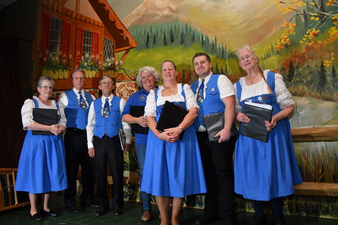 MARK NANCE/Sun-Gazette Long standing members of the Gesang Verein Harmonia include from left: 35 year member Kateri Cohick, Bob Fredrickson, 43 years, David Craig, 30 years, Lili Purewal, 20 years, Teri Kanecht, 35 years, director Michael Connor, and Ellie Laver, 26 years. The backstage mural of a German countryside was painted in 1967 by past member Gene Sortman.
