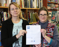 """PHOTO PROVIDED Kris Dickinson, left, and Kasey Cox Coolidge hold a copy of the letter signed by James Patterson and Oren Teicher that each one received along with a check. """"It's very clear that you have gone above-and-beyond in your work as a bookseller. We hope that this check will allow you to continue doing good work in your store and in your community,"""" the letter reads."""