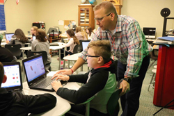 PHOTO PROVIDED Seventh-grade World History teacher Mr. Dustin Brouse works with a student on a new software program purchased for his World History Interactive Studio, funded by the WASDEF's Teacher Mini-Grant Program.