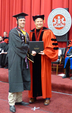 PHOTO PROVIDED Cecil Cooper, of Tioga, receives his diploma from Scott Barton, MU interim president.
