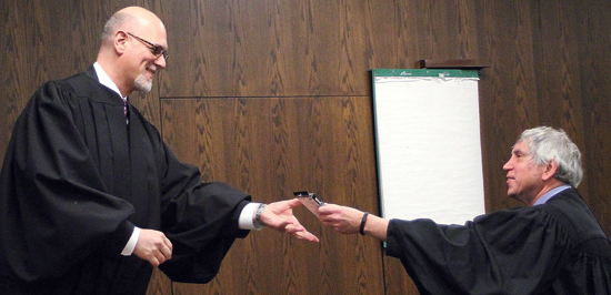 KAREN VIBERT-KENNEDY/Sun-Gazette Lycoming County Judge Eric R. Linhardt, left, receives a calculator from Senior Judge Kenneth D. Brown, right, during Linhardt's swearing in ceremony Tuesday morning at the Lycoming County Courthouse.