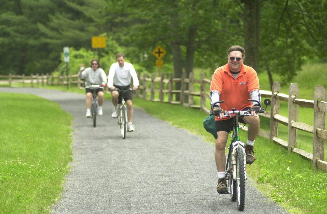 MARK NANCE/Sun-Gazette Cyclists enjoy a ride on the Rails to Trails north of Waterville.