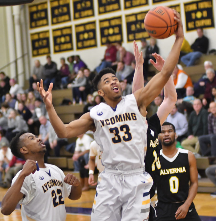 MARK NANCE/Sun-Gazette Lycoming's Devon Taylor grabs a rebound from Alvernia's Nicholas Youngkin (10) in the first half.