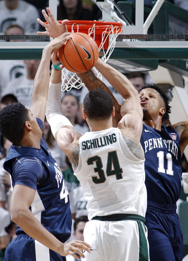 Penn State's Julian Moore, left, and Lamar Stevens, right, block a shot by Michigan State's Gavin Schilling (34) during the first half of an NCAA college basketball game, Wednesday, Jan. 31, 2018, in East Lansing, Mich. (AP Photo/Al Goldis)