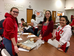 PHOTO PROVIDED The three club members volunteering at Firetree Place's Kids in the Kitchen event.