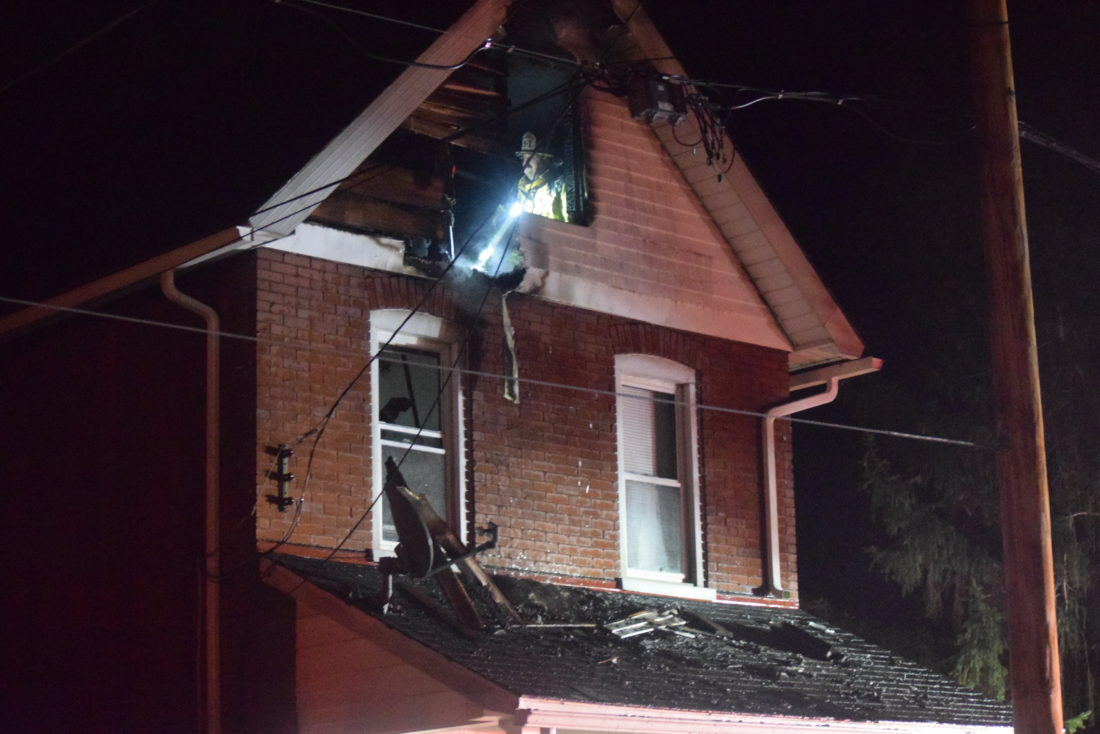 IOANNIS PASHAKIS/Sun-Gazette A city firefighter inspects the burned out attic of a home at 932 Mary St. The fire was brought under control around 9:30 p.m. Monday.