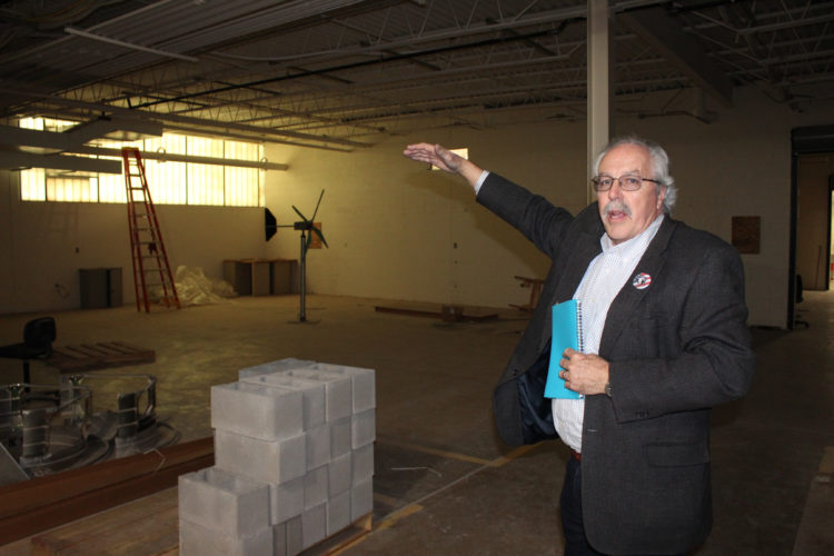 """CARA MORNINGSTAR/Sun-Gazette Tom F. Gregory, associate vice president for instruction at Pennsylvania College of Technology, talks about the new makerspace area and points out the early stages of construction for it inside the Kenneth E. Carl Building Technologies Center on the Penn College campus. He points to the """"clean space"""" side, which will feature carpeted floors."""