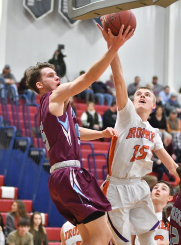 MARK NANCE/Sun-Gazette Loyalsock's Mitchell Klingerman (5) shoots around Danville's Mavin James (15) in the first quarter at Shikellamy during the HAC boys tournament championship game on Friday.