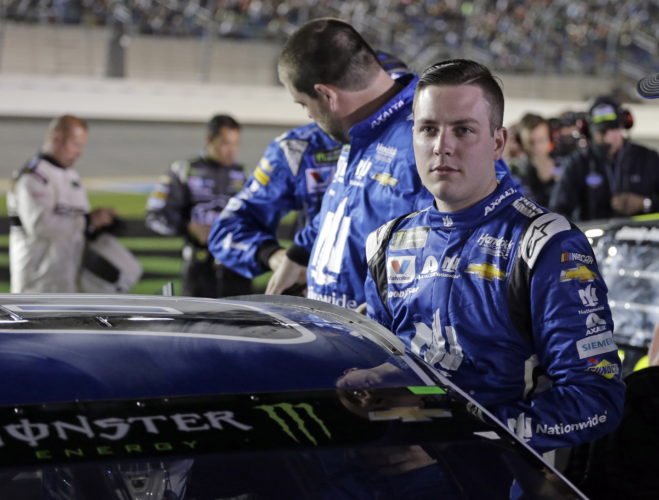 Alex Bowman climbs into his car before the first of two qualifying races for the NASCAR Daytona 500 auto race at Daytona International Speedway in Daytona Beach, Fla., Thursday, Feb. 15, 2018. (AP Photo/Terry Renna)