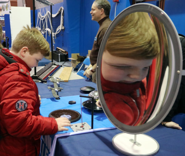 KAREN VIBERT-KENNEDY/Sun-Gazette  Fifth graders from area schools check out the various illusions using mirrors, including this concave mirror  at the Penn College Physics department table during the sneak peek of the Pennsylvania College of Technology Science Festival on Thursday.