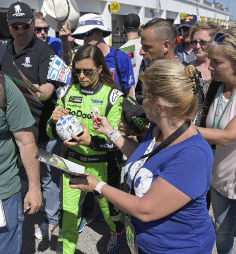 Danica Patrick, center, signs autographs after practice for the NASCAR Daytona 500 Cup Series auto race at Daytona International Speedway in Daytona Beach, Fla., Saturday, Feb. 17, 2018. Patrick has one last chance at a win in NASCAR, on its biggest stage, at the Daytona 500. She will run only that event, then focus on the Indianapolis 500 before she retires as a race car driver. (AP Photo/Phelan M. Ebenhack)