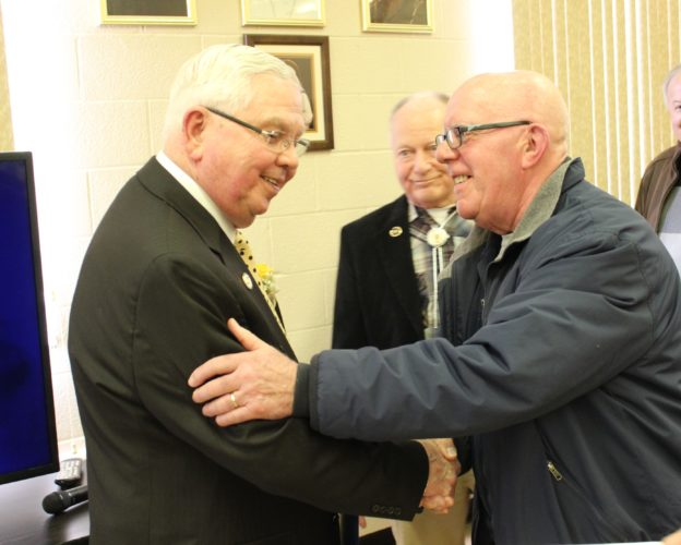 CARA MORNINGSTAR/Sun-Gazette John Dorin, left, shakes hands with Bill Dorman, right, as Gene Otterbein, center, looks on as they wish Dorin well in retirement after serving as Montoursville's mayor for the last 40 years at Dorin's retirement celebration at the Our Lady of Lourdes Banquet Hall, 100 Walnut St., Montoursville, on Sunday.