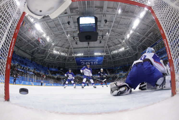 The puck shot by Ryan Donato (16), of the United States, sails past Jan Laco (50), of Slovakia, for a goal during the third period of the qualification round of the men's hockey game at the 2018 Winter Olympics in Gangneung, South Korea, Tuesday, Feb. 20, 2018. (AP Photo/Julio Cortez, Pool)