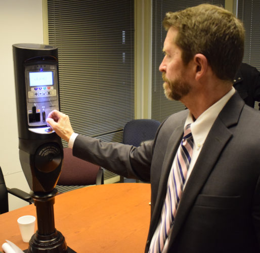 IOANNIS PASHAKIS/ Sun-Gazette Williamsport Parking Authority solicitor Scott Williams demonstrates that the new meters that the authority is hoping to purchase for the city light up after a payment is made.