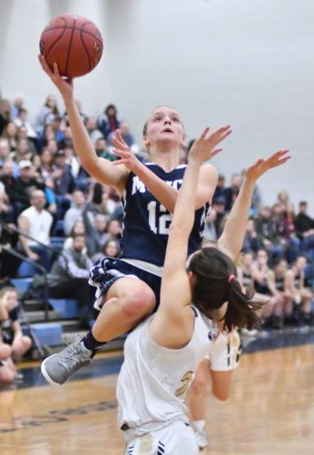 MARKNANCE/Sun-Gazette Muncy's Aleaha Bigelow (12) shoots over Southern Columbia's Hanna Davis (2) in the second quarter at Montoursville High School on Saturday.