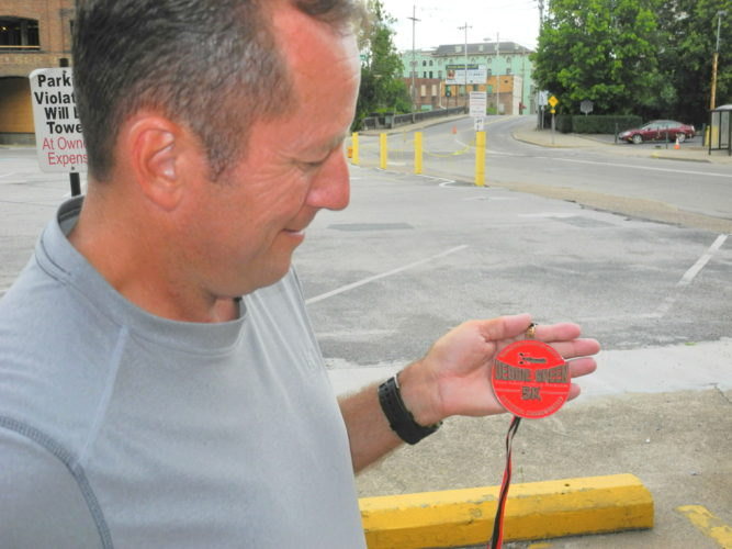 Photo by Heather Ziegler  Race director Ron Green holds one of the custom made finisher medallions that will be awarded after the Debbie Green Memorial 5K Run/Walk for Leukemia.