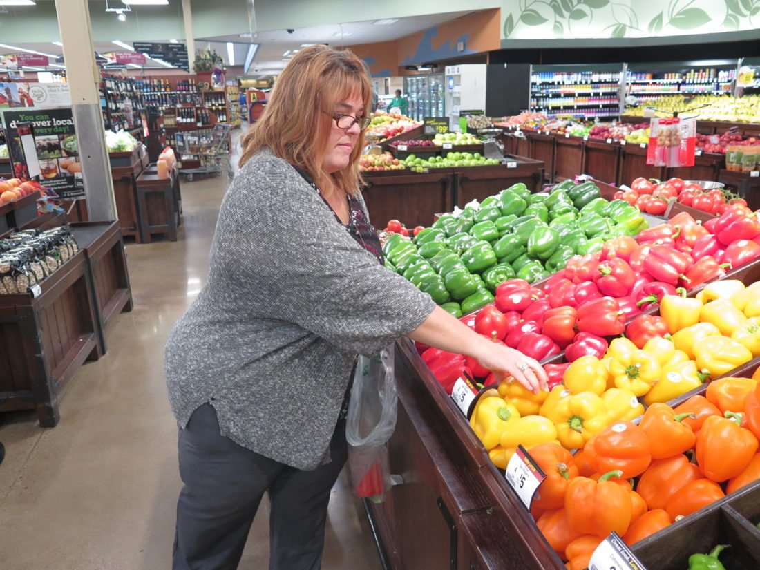 Christina Fisanick Greer selects a yellow pepper at Mount de Chantal Kroger in Wheeling. She eliminated refined sugar and processed foods and eats mainly       vegetables, fruits and beans.  Photo by Betsy Bethel