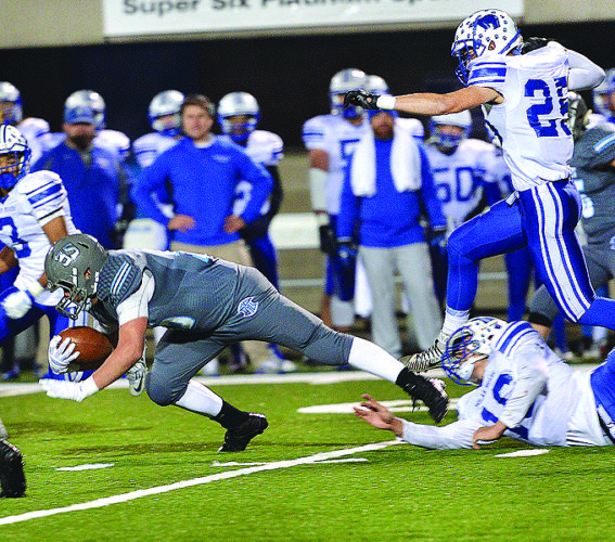 Photo by Scott McCloskey Mingo Central's Joe Hunt (35 is tackled by Fairmont Senior's Jake Abbott (16)during the W.Va. Class AAstate championship game.