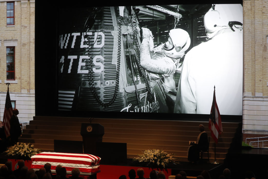 The casket of John Glenn rests below a screen displaying an archival photo of his boarding the Friendship 7 capsule during his funeral at The Ohio State University, Saturday, Dec. 17, 2016, in Columbus, Ohio. Glenn, the famed astronaut, died Dec. 8 at age 95. (AP Photo/John Minchillo)