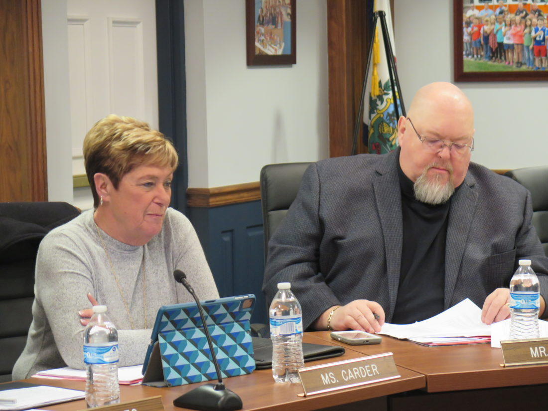 Photo by Joselyn King Ohio County Board of Education members Christine Carder and Tim Birch gather thoughts before the start of Monday night's board meeting.