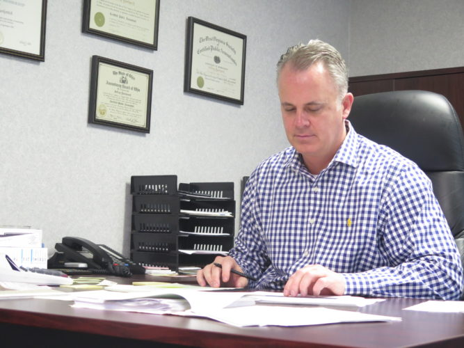 Photo by Alec Berry.  Jeff Yourkovich, of Yourkovich and Associates in Elm Grove, prepares a 2016 tax return in his office.