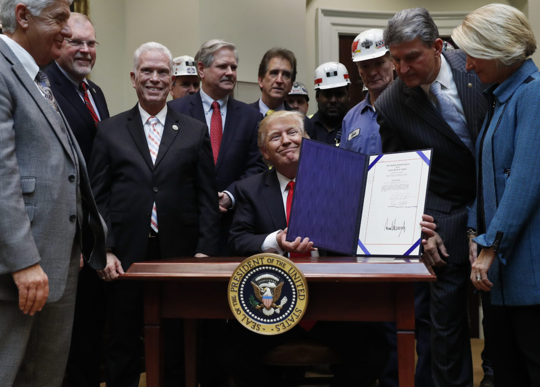 President Donald Trump, joined by coal miners and members of Congress including Sen. Shelley Moore Capito, R-W. Va., right, Sen. Joe Manchin, D-W. Va., second from right, and Rep. Bill Johnson, R-Ohio, third from right, holds up H.J. Res. 38 after signing it in the Roosevelt Room of the White House in Washington, Thursday, Feb. 16, 2017. (AP Photo/Carolyn Kaster)