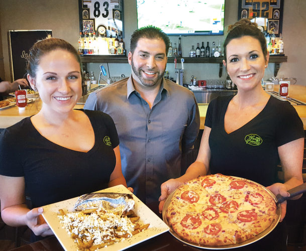 Theo Yianni's  Co-Owner Shawn Mihellis, center, along with servers, Lizzie Strain, left and Brittany Sutton,  display a gyro with Greek fries, along with a brick oven made pizza.  Photo by Scott McCloskey