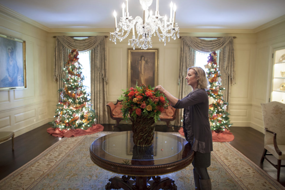 "In this Dec. 1, 2010 photo provided by Stichting Kunstboek, Laura Dowling completes a holiday arrangement of peach and coral roses in a magnolia leaf vase in the Vermeil Room, before the launch of the White House Christmas season, with the Aaron Shikler portrait of First Lady Jacqueline Kennedy in the background at the White House in Washington. The photograph is featured in the book ""Floral Diplomacy: At the White House,"" by Laura Dowling. (Chuck Kennedy/The White House/Stichting Kunstboek via AP)"