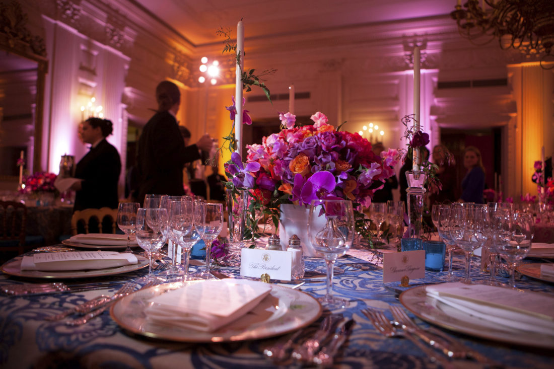 "In this Feb. 27, 2011 photo provided by Stichting Kunstboek, a vivid bouquet of orange and fuchsia flowers with accents of hot pink phaleonopsis orchids makes a strong statement for the annual National Governors Association Dinner at the White House state dining room in Washington. The historic ""Charleston"" candlesticks are wrapped with blooming jasmine vine. The Lady Bird and President Johnson china service, featuring wildflowers from across America, reflects the gathering of Governors from all 50 states. The photograph is featured in the book ""Floral Diplomacy: At the White House,"" by Laura Dowling. (Chuck Kennedy/The White House/Stichting Kunstboek via AP)"