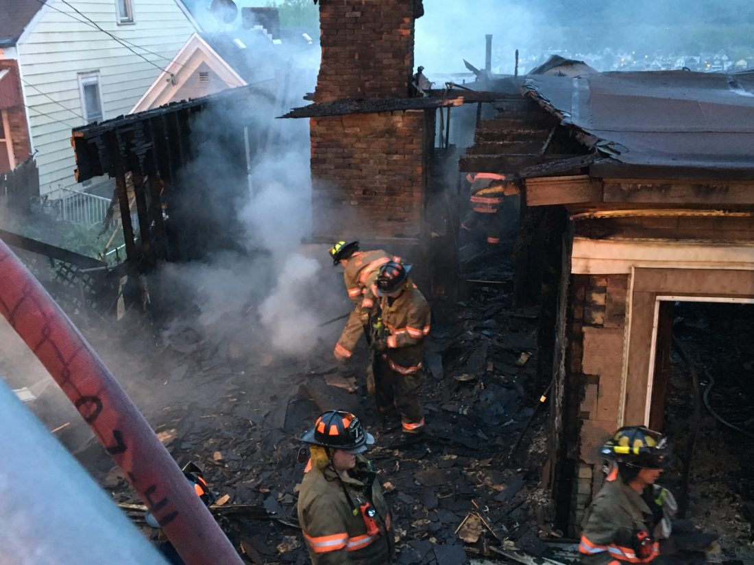 Photo by Heather Ziegler Firefighters dig through the remains of the burned out structure. Crews kept the fire from spreading to the neighboring occupied homes.