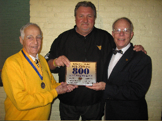 Photo by Bubba Kapral BMAC members John Budinscak, left, and John S. Marshall presented WVU men's basketball coach Bob Huggins with a special plaque, commemorating his 800 career wins, during Monday night's caravan trip to Wheeling.