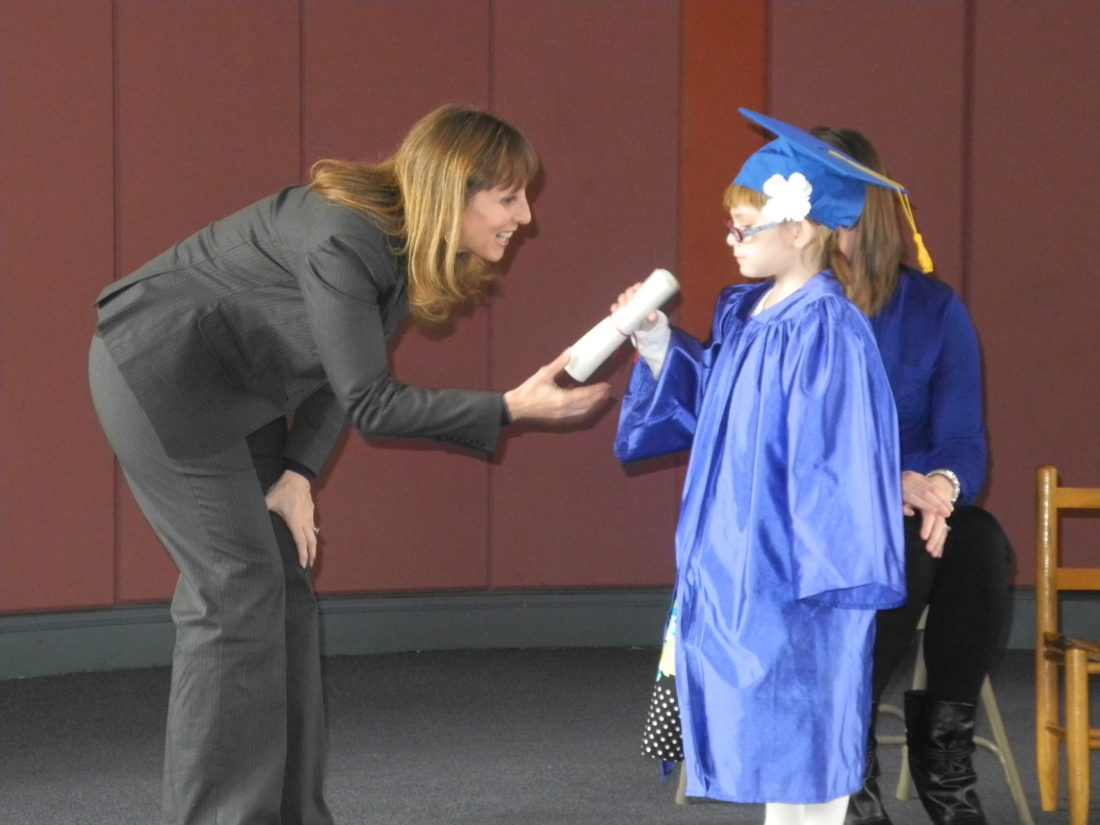 File photo Kathy Shapell, executive director of the Augusta Levy Learning Center, presents a diploma to then-6-year-old Chloe Milliken during a 2013 graduation ceremony.