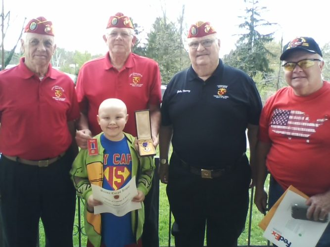 Photo Provided Marine veterans from left, Fred Brunner, Stephen Duncil, John Nanny and Larry Alexander are shown after they presented cancer patient Dominic Alexander, 8, with a Purple Heart medal that Duncil earned during his military service in Vietnam.