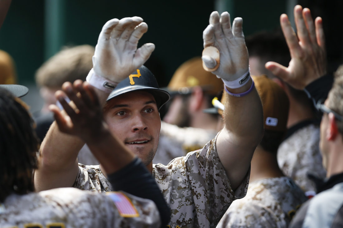 Pittsburgh Pirates' Adam Frazier is greeted by teammates in the dugout after scoring on a sacrifice fly by Josh Harrison in the sixth inning of a baseball game against the Washington Nationals, Thursday, May 18, 2017, in Pittsburgh. Frazier had three hits in five at bats, scored two twice, and drove in four runs in the Pirates' 10-4 win. (AP Photo/Keith Srakocic)