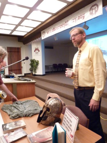 Photo by Linda Comins Lunch With Books patrons examine a Viking helmet and chain mail armor after a presentation by Dr. Darrin Cox, at right.
