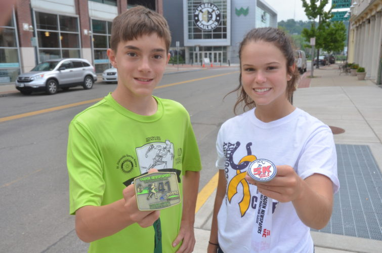 Photo by Scott McCloskey Parker Skedel, 14, left, displays the medal that will be awarded to all Ogden Newspapers Half Marathon Classic finishers on Saturday, while Jamie Fogle, 17, holds up the medal that all 5K Run/Walk finishers will receive.