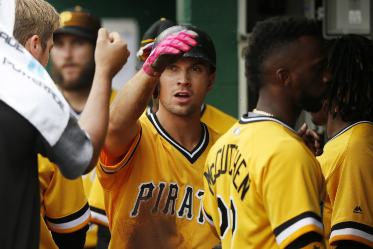 Pittsburgh Pirates' Adam Frazier, center, is congratulated by teammates in the dugout after scoring in the sixth inning against the Philadelphia Phillies during a baseball game in Pittsburgh, Sunday, May 21, 2017. (AP Photo/Jared Wickerham)
