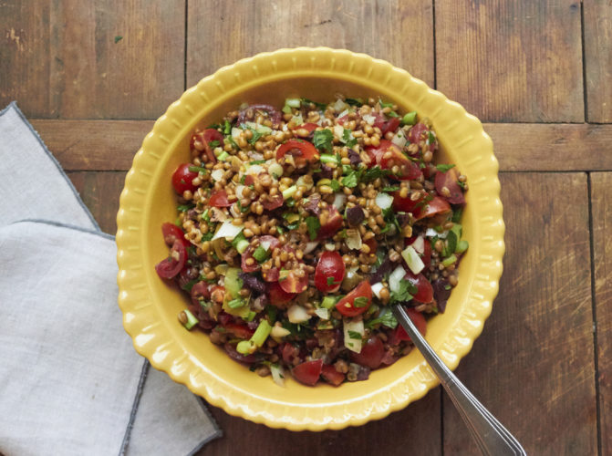 This December 2016 photo shows a Mediterranean tomato wheat berry salad with fresh herbs in New York. This dish is from a recipe by Katie Workman. (Mia via AP)