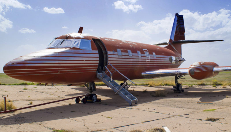This undated photo provided by GWS Auctions, Inc. shows a private jet once owned by Elvis Presley, on a runway in New Mexico. The plane is set to be auctioned after sitting on a runway in New Mexico for 30 years. GWS Auctions Inc. out of California is holding the auction for the plane on May 27, 2017 at an event featuring A-list celebrity memorabilia. The interior was designed by Elvis Presley, with gold-tone, woodwork, inlay and red velvet seats and red shag carpet. However, the plane has no engine and the cockpit has not been restored. (GWS Auctions, Inc. via AP)