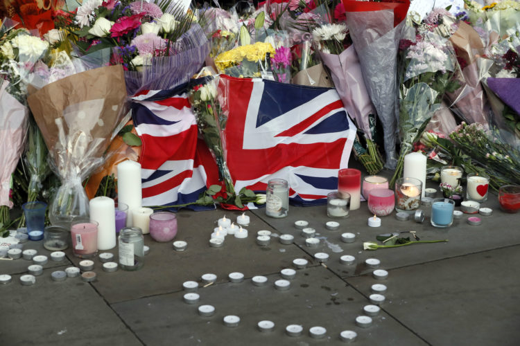 Flowers and candles are seen after a vigil in Albert Square, Manchester, England, Tuesday May 23, 2017, the day after the suicide attack at an Ariana Grande concert that left 22 people dead as it ended on Monday night. (AP Photo/Kirsty Wigglesworth)